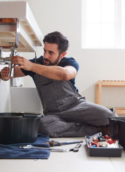 male-plumber-working-to-fix-leaking-sink-in-home-.jpg